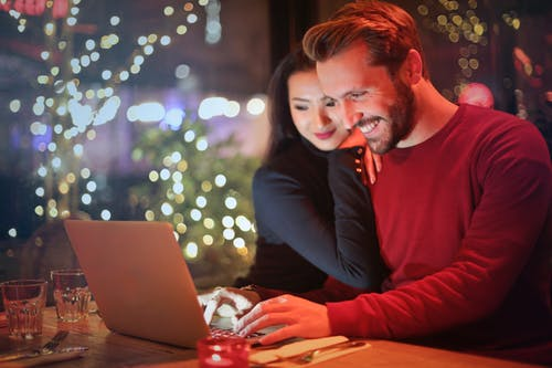 Couple happily working on their finances because they've each discovered how to communicate with your spouse about money.