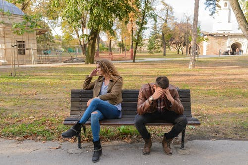 Unhappy couple sitting on a bench struggling with the question of why stay in an unhappy marriage.