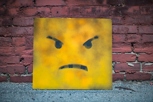 Yellow square metal face that appears to be feeling contempt.