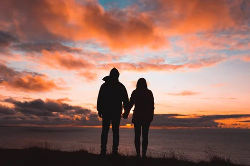 Couple holding hands walking into the sunset because they've each finally answered the question is my marriage worth saving.