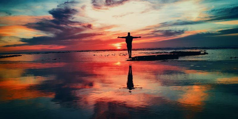 Person feeling the power of a strong sense of self with arms outstretched standing on the beach at sunset