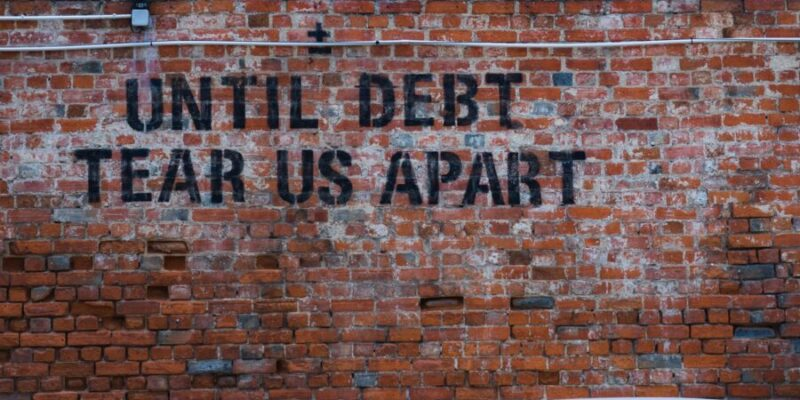 "Brick wall with the words ""Until Debt Tear Us Apart"" written on it."