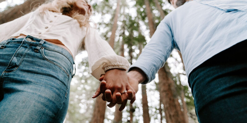 Couple holding hands in a forest as they discuss attending a private couples marriage retreat.