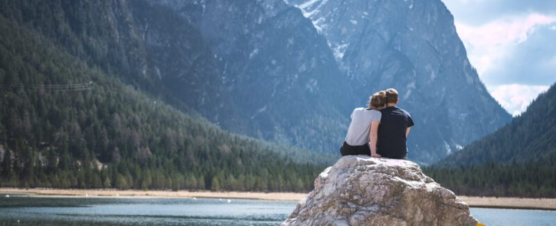 Couple sitting on a boulder and overlooking a mountain stream.